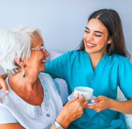 caregiver giving tea to senior woman