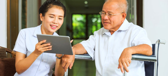 caregiver and senior man looking at the tablet