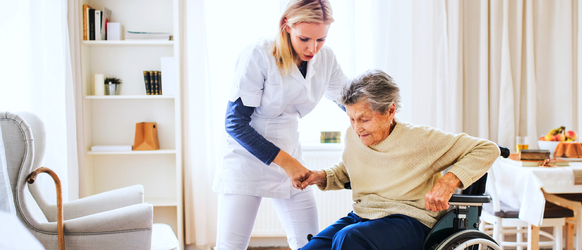caregiver helping senior woman get up