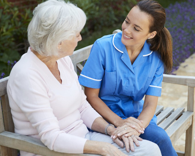 a senior woman and a caregiver sitting on a bench talking