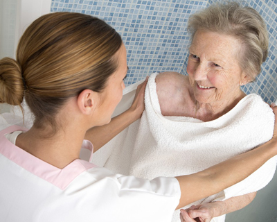 a caregiver drying off a senior woman with a towel