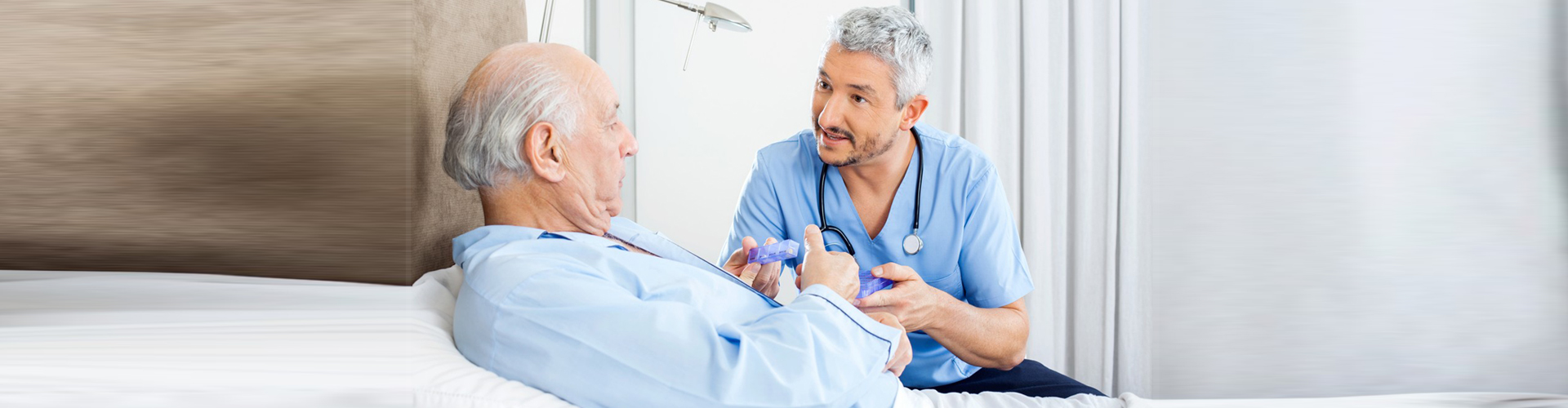 a nurse giving medicine to a senior man
